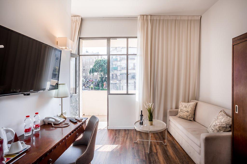 פנים החדר עם ספת ישיבה שידת כתיבה וטלויזיה